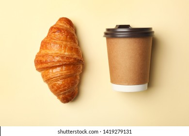 Paper coffee cup and croissant on color background, flat lay. Mockup for design