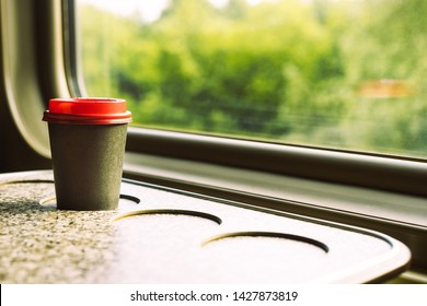 A paper coffee cup with a red plastic lid and a white inscription circle. Coffee to go on a table in the train overlooking a beautiful rural green landscape. Travel, lifestyle