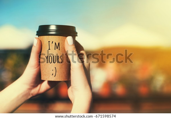 Paper coffee cups in woman's hands with text I'M YOURS.
