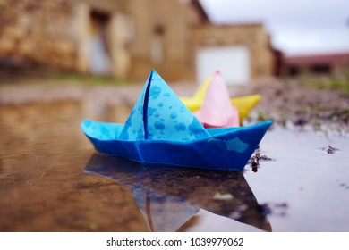 Paper color boats in a puddle