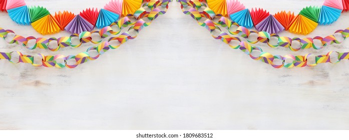 Paper colorful chain garland over white wooden background. Traditional jewish sukkot holiday decoration