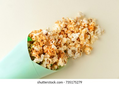 Paper cone with tasty caramel popcorn on light background