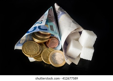 Paper cones with sugar cubes in one and money (euro and pound notes and euro cents coins) symbolising sugar tax in EU