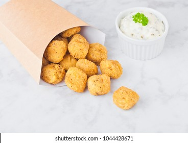 Paper container with fried crispy chicken popcorn nuggets on marble background with sauce