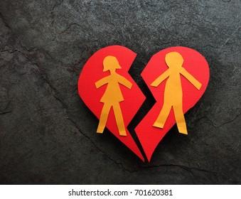 Paper couple on broken red heart