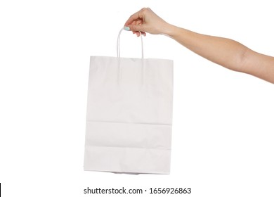 Paper craft bag, eco packaging in a female hand, isolated on white background, with place for text. concept of shopping, gift