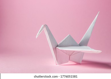 paper crane on a pink background. A white paper crane lies on the right side. Place for an inscription or logo. DIY Origami
