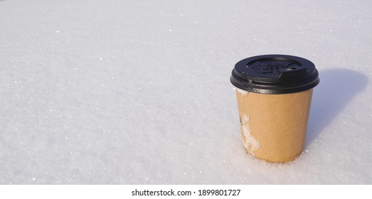 Paper cup with aromatic, hot latte coffee on fluffy, frosty snow. Aromatic composition with natural.