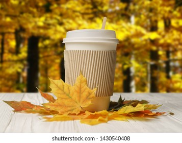 Paper cup and autumn leaves on white wood table with autumn forest bacground.