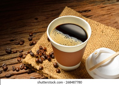 Paper cup of coffee and coffee beans on wooden table