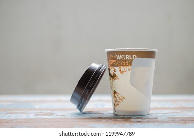 paper cup of coffee with cap on wood table,cup handle.