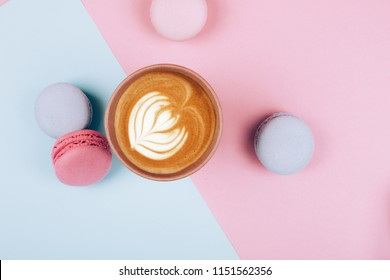Paper cup of coffee to go with macaron on pink and blue background from above, flat lay