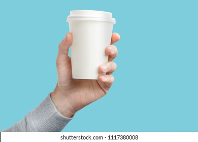 A paper cup of coffee in the hand. White paper cup of coffee in hand. For mock up. Isolated. On colored background