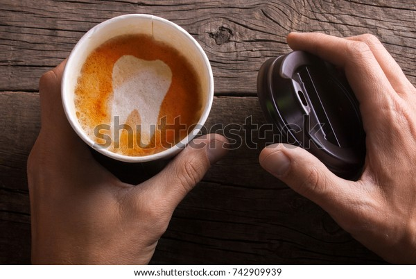 Paper cup of coffee is held by a man in his hand. Coffee makes teeth yellow and sick.