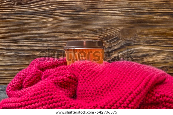 Paper cup of coffee in knitted scarf. Winter cold season concept.