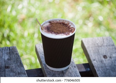 Paper cup with coffee on the bench in park