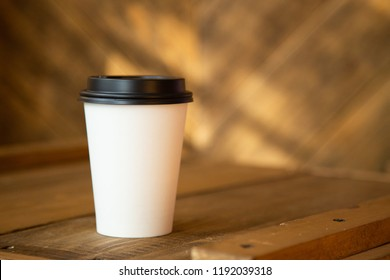 Paper Cup of coffee on wooden wall background