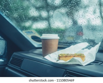 A paper cup of coffee and a slice of cake on the dashboard of a car on a rainy day