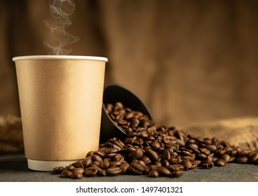 Paper cup of coffee with smoke and coffee beans