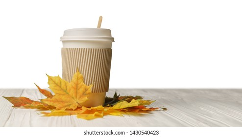 Paper cup of coffee or tee to go take away mug fast food and autumn leaves on white wood