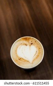 Paper cup with heart shaped cappuccino foam on a wooden table