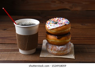 A paper cup of hot fresh brewed coffee next to a stack of fancy donuts.