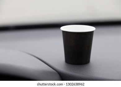 Paper cup on the front of the car. Background is blurred.