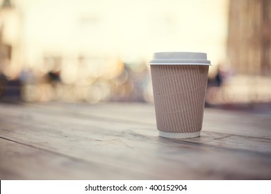 Paper cup on wooden table on street food festival