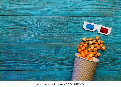 Paper cup with popcorn and 3D glasses on blue background. Top view.