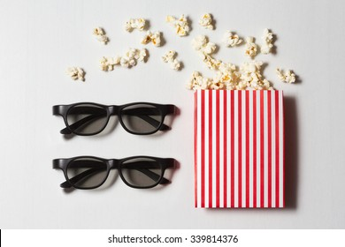 ef899cfaf6a5 paper cup with popcorn and 3D glasses on white background. mock up. top view