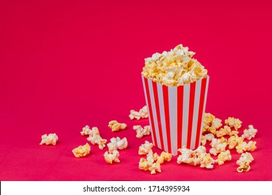 Paper cup with popcorn on color background. Striped box with popcorn on red background.Popcorn in red and white striped cardboard bucket .