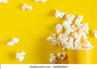 Paper cup with popcorn on yellow background. Flat lay, top view, copy space