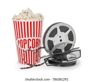 Paper cup with tasty popcorn, glasses and movie reel on white background