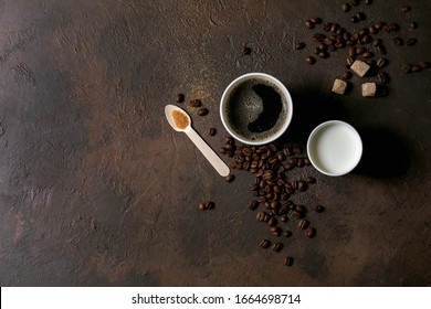 Paper cups of americano coffee and milk, recycled wooden spoon of cane sugar, coffee beans over dark texture background. Flat lay, space