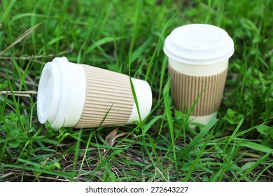 Paper cups on green grass background