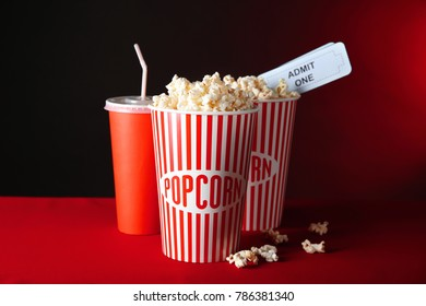 Paper cups with tasty popcorn, tickets and drink on table against dark background