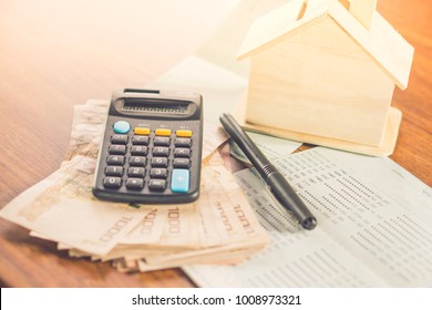 paper currency,calculator,saving account and house model on desk, concept of buy ,rent,pay tax for home