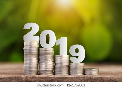 Paper cut of 2019 New year on coins stack for saving money and financial planning concept