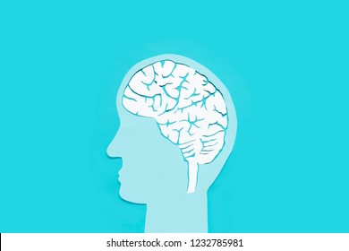 Paper cut is a brain shape. Face shapes and brain are the main components of the work.The background is blue.