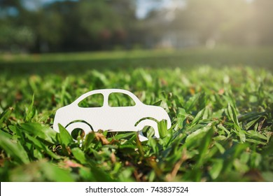 Paper cut of car on green grass background, earth day eco green energy concept with copy space, spring time, background and banner