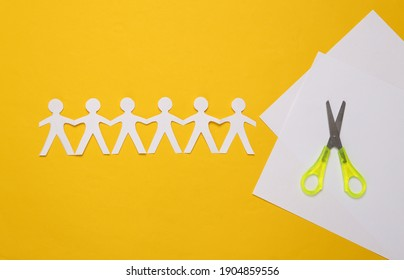 Paper cut chain of people with scissors on yellow background