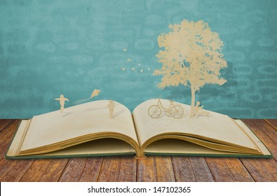 Paper cut of children play on old book