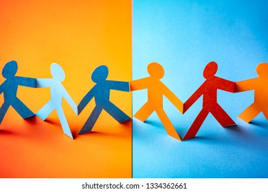 Paper cut concept - multicultural cooperation of the two groups. Orange and blue contrast colors.
