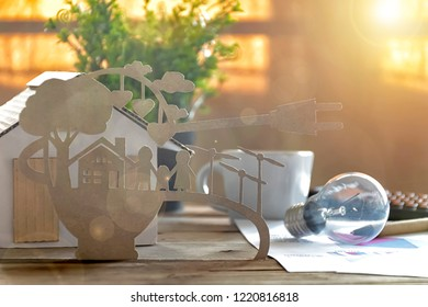 Paper cut of eco on desk. Home model, lamp, pen, document Stories about energy saving, happy families using clean electrical energy.