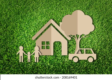 Paper cut of family on green grass