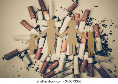 paper cut of family on pile of cigarettes / drugs destroying family concept
