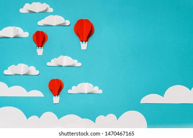 Paper cut objects composition with hot air balloons, clouds, and sun. Creative concept for banner/landing/background designs.
