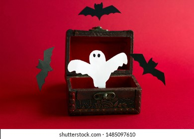 paper cut scary ghost and bats   fly out of an old vintage  wooden chest on a black background, festive Halloween card