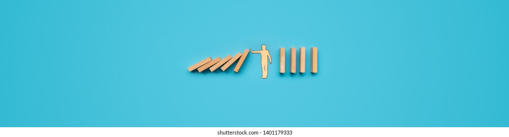 Paper cut silhouette of a paper man stopping dominos from falling. Wide view image over blue background.