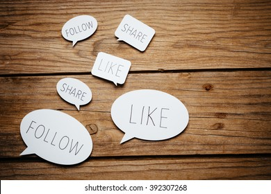 Paper cut speech bubbles with social media concepts on wooden background.